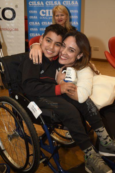 MARTINA GUSMÁN abraza a un de beneficiario que le hace entrega de un obsequio